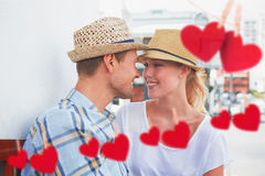 Composite image of young hip couple sitting on bench about to kiss Stock Photo