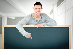 Composite image of young male pointing at banner below him Stock Images