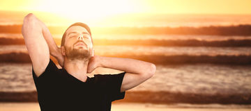 Composite image of young man with eyes closed against white background. Young man with eyes closed against white background against image of a sunset over the Royalty Free Stock Photos