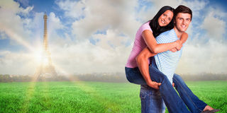 Composite image of young man giving girlfriend a piggyback ride Stock Photo