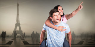 Composite image of young man giving girlfriend a piggyback ride royalty free stock images