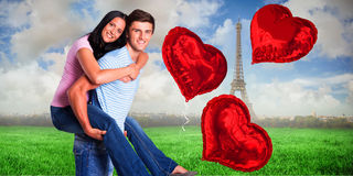 Composite image of young man giving girlfriend a piggyback ride Stock Photography