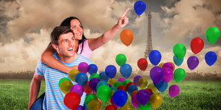 Composite image of young man giving girlfriend a piggyback ride Royalty Free Stock Photo