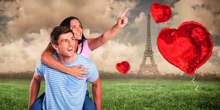 Composite image of young man giving girlfriend a piggyback ride Stock Images