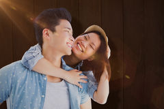 Composite image of young man giving piggyback ride to woman Royalty Free Stock Images