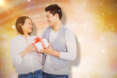Composite image of young man giving present to woman Royalty Free Stock Photo