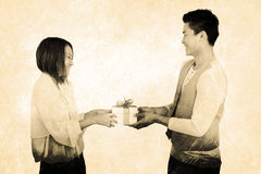 Composite image of young man giving present to woman Stock Photo
