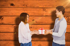 Composite image of young man giving present to woman Stock Images