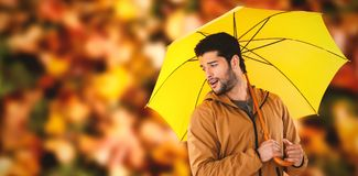 Composite image of young man holding yellow umbrella Royalty Free Stock Images