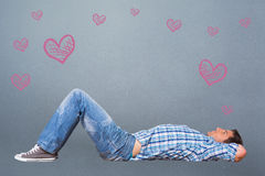 Composite image of young man lying on floor thinking Royalty Free Stock Photo