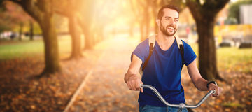 Composite image of young man riding bicycle Royalty Free Stock Photo