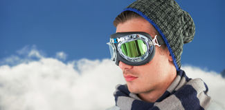 Composite image of young man wearing aviator goggles against white background. Young man wearing aviator goggles against white background against mountain top stock image