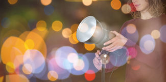 Composite image of young photographer holding focus light. Young photographer holding focus light against close-up of lighting royalty free stock images