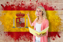 Composite image of young pretty student pointing and reading Royalty Free Stock Images