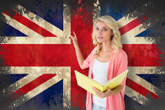 Composite image of young pretty student pointing and reading Stock Images