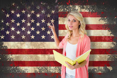 Composite image of young pretty student pointing and reading Stock Photography