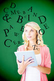 Composite image of young pretty student using tablet pc Royalty Free Stock Images