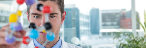 Composite image of young scientist experimenting molecule structure Stock Image