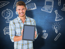 Composite image of young student showing tablet pc. Young student showing tablet pc  against blue chalkboard Royalty Free Stock Photo
