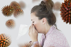 Composite image of young woman blowing her nose. Young woman blowing her nose against virus stock image