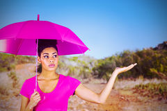 Composite image of young woman carrying pink umbrella. Young woman carrying pink umbrella  against mountain trail Stock Photo