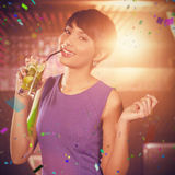 Composite image of young woman dancing on dance floor while having cocktail Royalty Free Stock Images