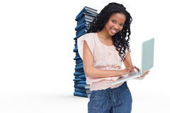 Composite image of a young woman holding a laptop is smiling at the camera Royalty Free Stock Photos