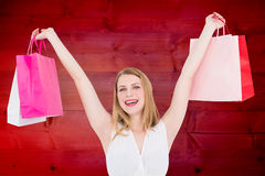 Composite image of young woman holding up shopping bags Stock Images