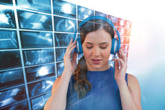 Composite image of young woman listening to music on headphones with closed eyes. Young woman listening to music on headphones with closed eyes against generated Royalty Free Stock Photos