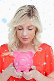 Composite image of young woman looking at a piggy bank held by her hands Stock Image