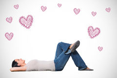 Composite image of young woman lying on floor thinking Stock Image