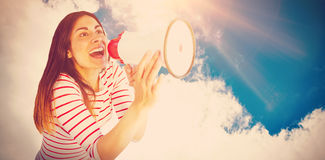 Composite image of young woman shouting with megaphone. Young woman shouting with megaphone against low angle view of sky Stock Images