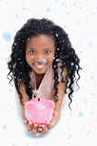 Composite image of a young woman smiling at the camera is holding a piggy bank in her hands Royalty Free Stock Images