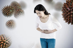 Composite image of young woman with stomach pain. Young woman with stomach pain against white background with vignette royalty free stock image