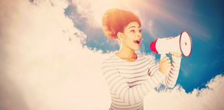 Composite image of young woman using megaphone for making announcement. Young woman using megaphone for making announcement  against low angle view of sky Stock Image