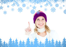 Composite image of young woman wearing a colorful hat pointing upwards with her finger Royalty Free Stock Photos