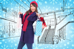 Composite image of young woman in winter clothes posing with shopping bags Stock Photo