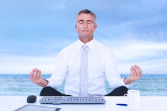 Composite image of zen businessman meditating in lotus pose Royalty Free Stock Image