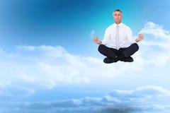 Composite image of zen businessman meditating in lotus pose Royalty Free Stock Photos