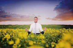 Composite image of zen businessman meditating in lotus pose Stock Photo