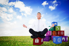 Composite image of zen businessman meditating in lotus pose Royalty Free Stock Photos