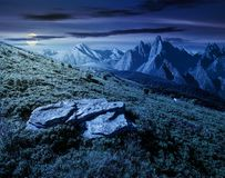 Composite of meadow in rocky mountains at night. In full moon light. beautiful unrealistic landscape in summertime royalty free stock photography