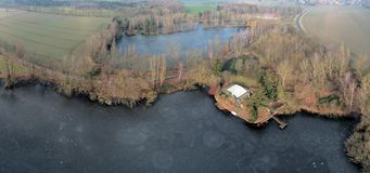 Composite panorama of aerial photographs and aerial photos of two small ponds between meadows and fields with a grill hut and fish royalty free stock image