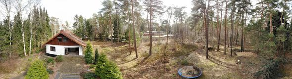 Composite panorama from aerial photos with a drone in low heights, detached house from the seventies on a forest property, old bro. Ken trampoline for the Royalty Free Stock Image