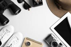 Composition étendue plate avec le comprimé, les jumelles et la caméra sur le fond blanc, l'espace pour le texte image libre de droits