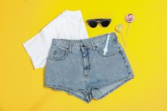 Composition étendue plate avec : vêtements de femmes et accessoires, cannes de sucrerie sur le fond jaune images libres de droits