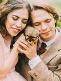 Composition étonnante des nouveaux mariés tenant et choyant le beau furet brun Photo en gros plan Image stock