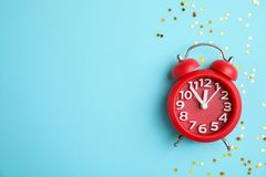 Composition with alarm clock and confetti on color background. Christmas countdown Royalty Free Stock Photography