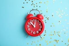 Composition with alarm clock and confetti on color background. Christmas countdown Stock Image