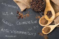Composition of allspice on a stone countertop. And inscriptions mentioning its advantages royalty free stock photo